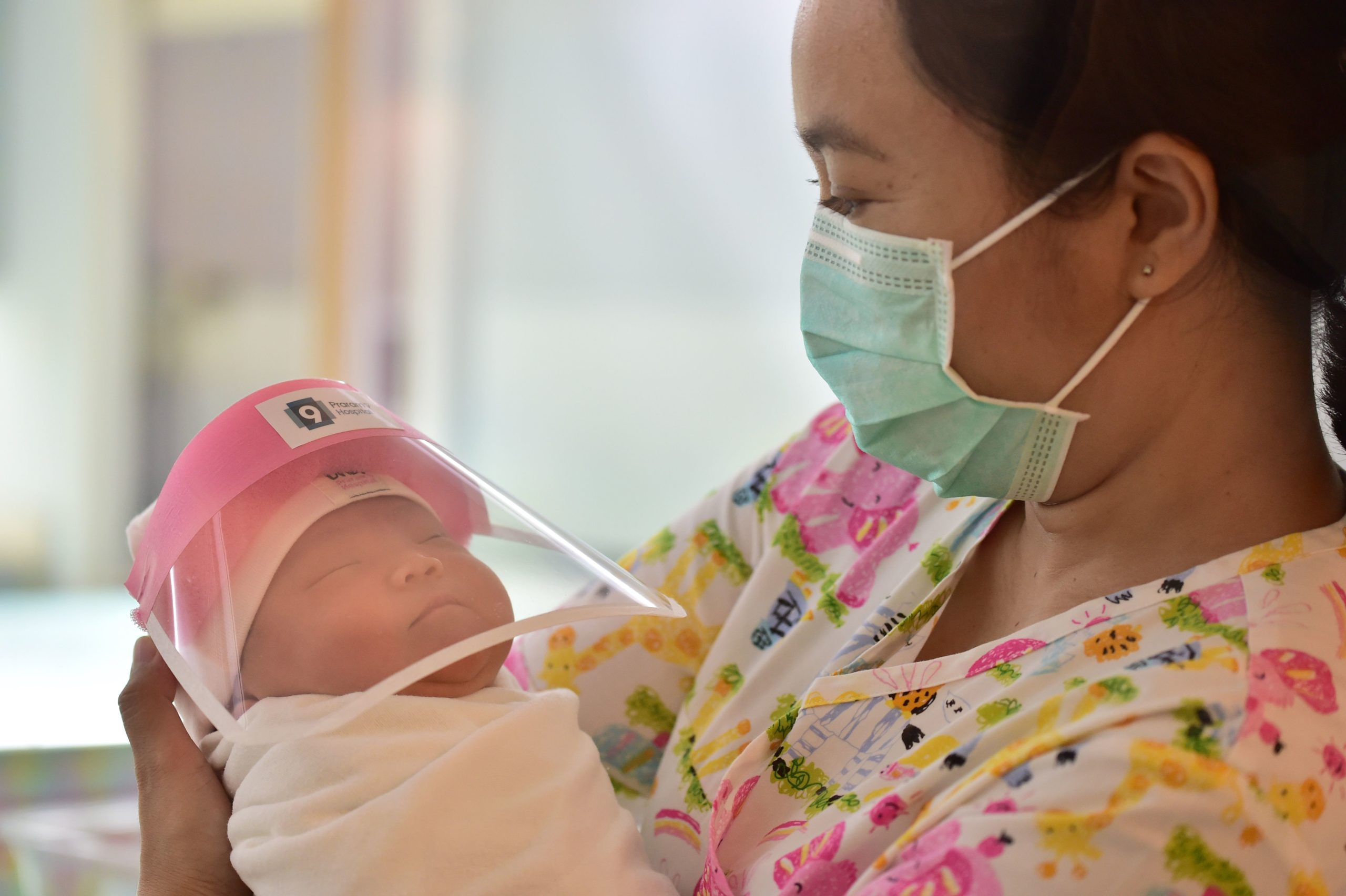 A nurse holding a newborn baby wearing a face shield, in an effort to halt the spread of the COVID-19 coronavirus