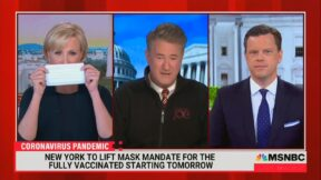 Mika Brzezinksi holds a mask next to Joe Scarborough and Willie Geist