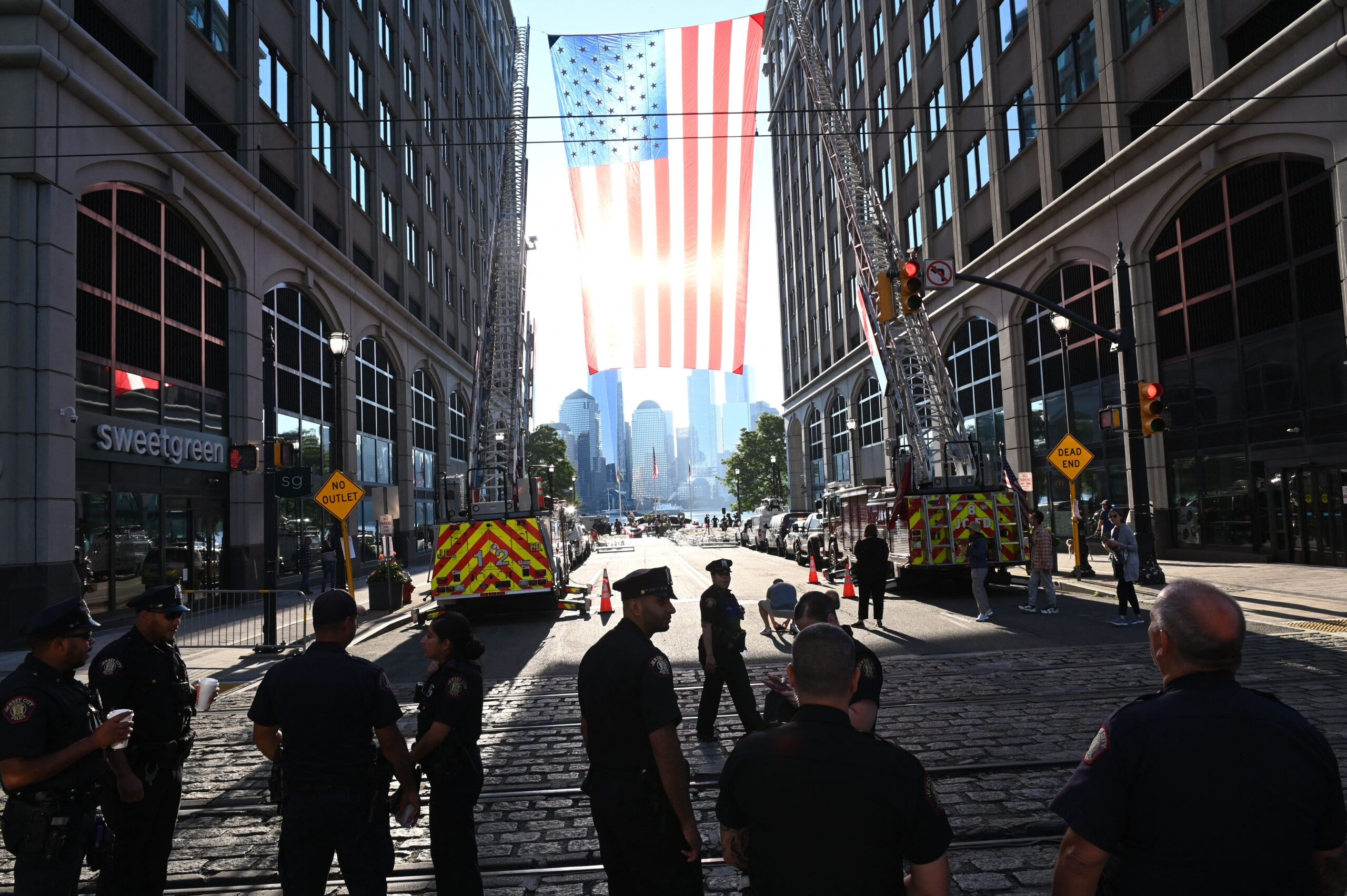 Firefighters from the New Jersey Fire Department march near an oversized American flag hoisted near the Hudson River.